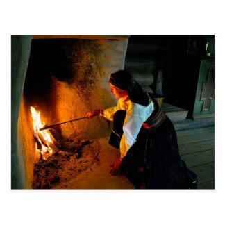 Postal Mujer noruega que tiende el fuego del hogar
