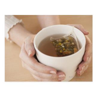 Postal Mujer que sostiene la taza con té de manzanilla