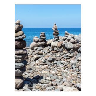 Postal Piedras apiladas de la playa en el mar azul