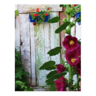Postal Puerta azul griega en jardín de flores en Grecia
