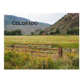 Postal puerta roja por una pradera en Colorado