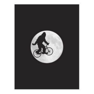 Postal Squatch en una bici en cielo con la camiseta de la