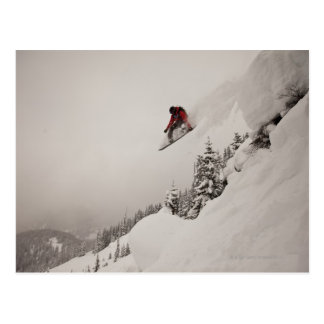 Postal Un snowboarder salta de un acantilado en polvo