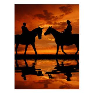 Postal Vaqueros del montar a caballo en puesta del sol