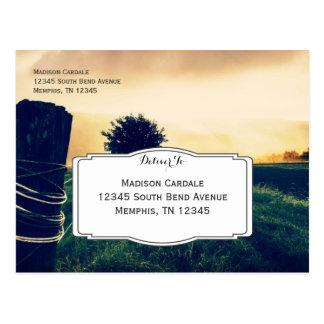 Poste de la cerca del campo del país que casa las postal