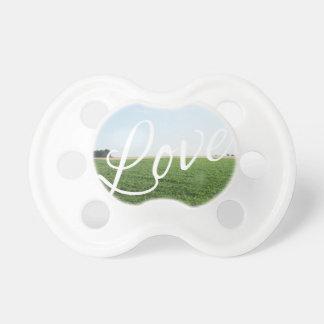 Prado herboso de la naturaleza de la tipografía de chupete de bebe