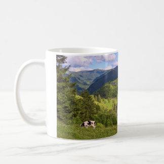 Prados verdes y una vaca con la opinión del taza de café