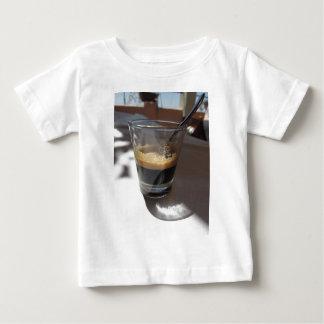 Primer del café del café express en una taza de camiseta de bebé