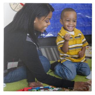 Profesor con el niño en guardería azulejo