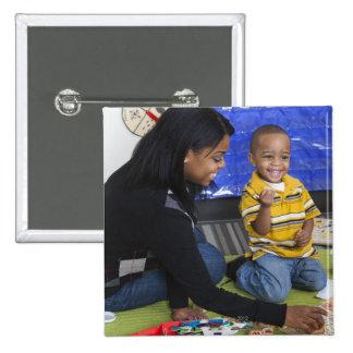 Profesor con el niño en guardería chapa cuadrada