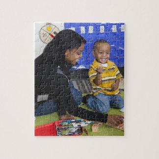 Profesor con el niño en guardería puzzles