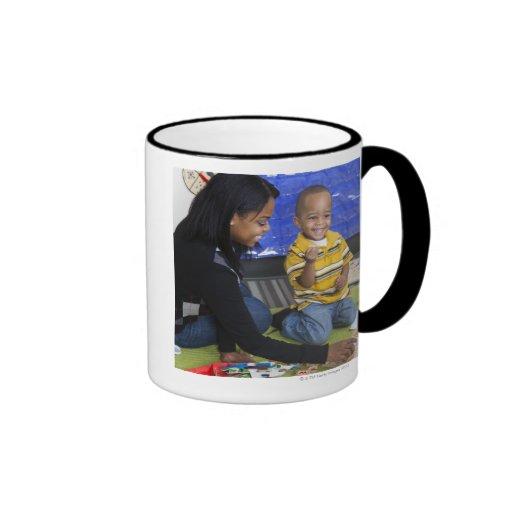 Profesor con el niño en guardería tazas de café