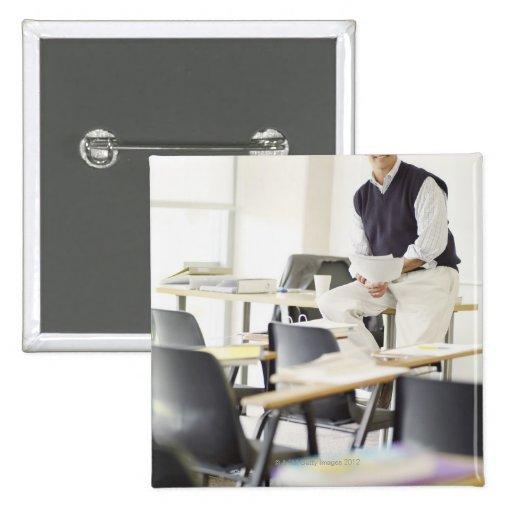 Profesor confiado que se inclina en el escritorio  pins