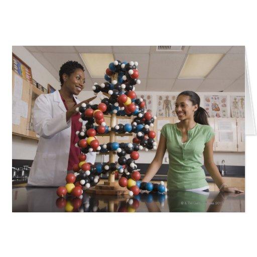 Profesor de ciencias y adolescente que miran tarjetón