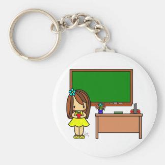 Profesor lindo en su sala de clase que sostiene un llavero redondo tipo chapa
