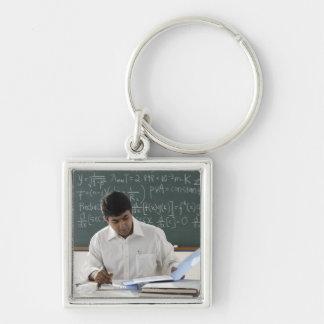 profesor que se sienta en el escritorio, trabajand llaveros personalizados