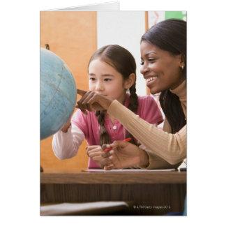 Profesor y estudiante que miran el globo felicitacion