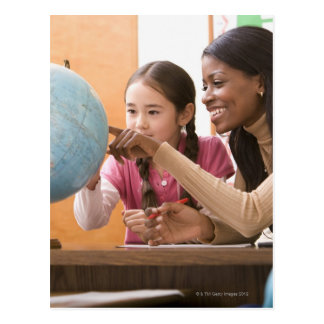 Profesor y estudiante que miran el globo postales