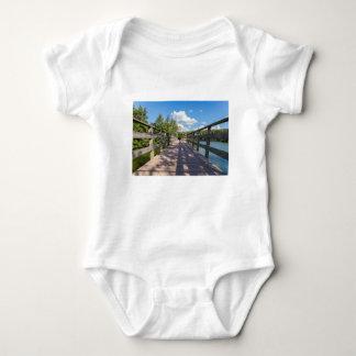 Puente de madera largo sobre el agua de la charca body para bebé