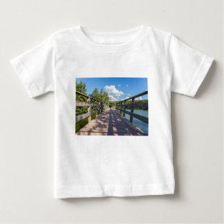 Puente de madera largo sobre el agua de la charca camiseta de bebé