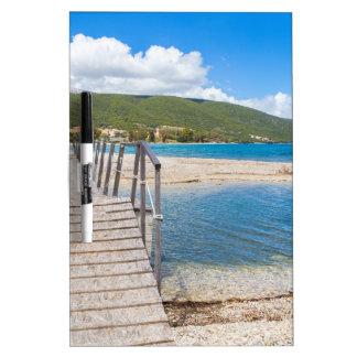 Puente peatonal de madera en la playa griega pizarra blanca