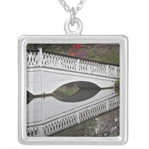 Puente que refleja en la charca, magnolia pendientes