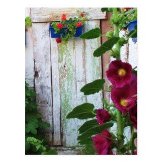 Puerta azul griega en jardín de flores en Grecia Postal