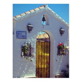 Puerta española roja del estilo, flores de postal
