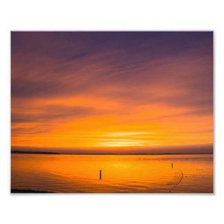 Puesta del sol anaranjada real sobre el lago fotografias