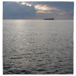 Puesta del sol caliente del mar con el buque de servilleta de tela