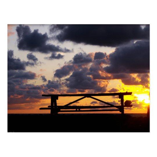 Puesta del sol con la mesa de picnic postal