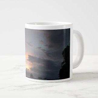 Puesta del sol durante la estación de la monzón taza de café gigante