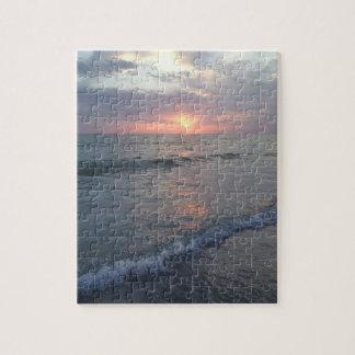 Puesta del sol en el rompecabezas de la playa