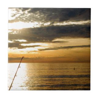 puesta del sol pacífica de oro azulejo