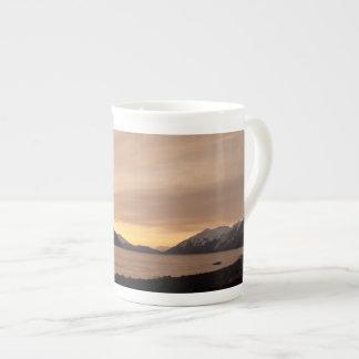 Puesta del sol sobre bahía de la fábrica de conser taza de porcelana
