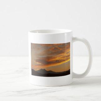 Puesta del sol sobre los picos gemelos taza básica blanca