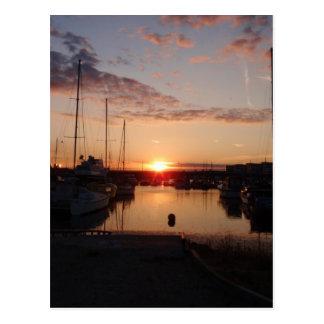Puesta del sol sobre un puerto deportivo postal