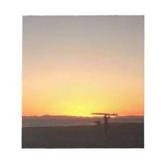 Puesta del sol y libreta de la tabla hawaiana