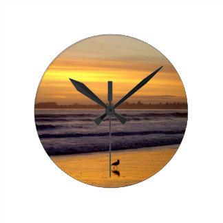 Puesta del sol y reloj de pared del pájaro