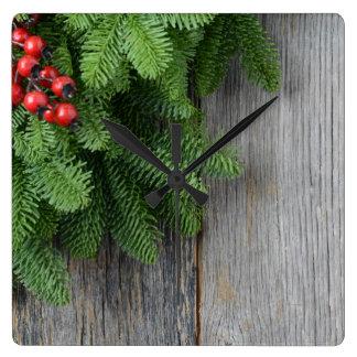 Rama de árbol de navidad con la baya del acebo reloj cuadrado