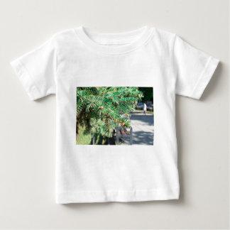 Rama de la conífera en la calle de la ciudad camiseta de bebé