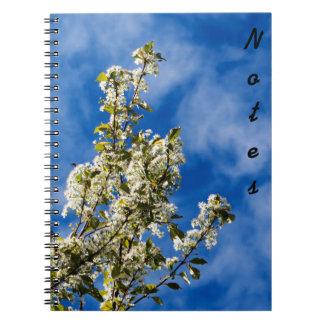 Ramas de árbol por completo de las flores blancas cuaderno
