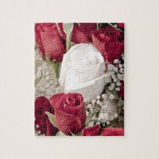 ramo de rosas rojos con un rosa blanco en el puzzle
