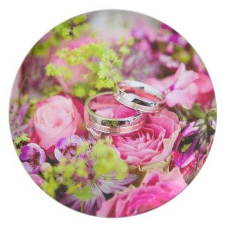 Ramo del boda con las bandas del anillo de bodas plato