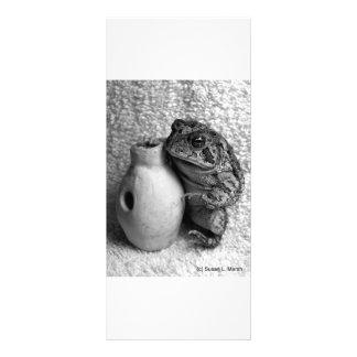 Rana del sapo que sostiene la fotografía de la tarjeta publicitaria