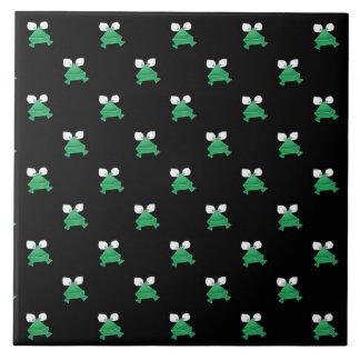 Ranas verdes en la baldosa cerámica negra