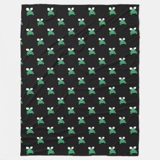 Ranas verdes en la manta negra del paño grueso y