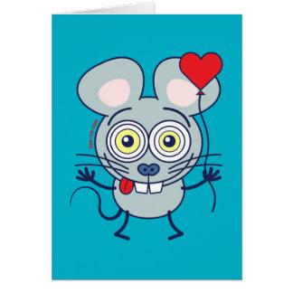 Ratón divertido que sostiene un globo y que siente tarjeta de felicitación
