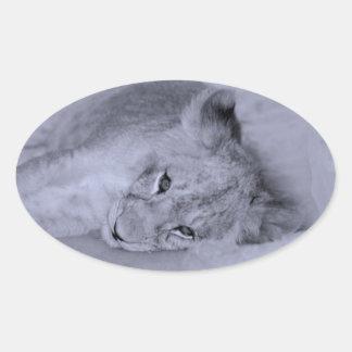 Reclinación adorable del cachorro de león pegatina ovalada