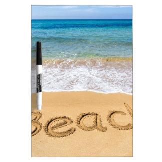 Redacte la playa escrita en arena en el mar griego pizarra blanca
